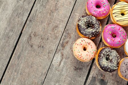 Glazed donuts on wooden background. Creative photo.