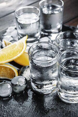 Vodka in shot glasses on rustic wood background Standard-Bild