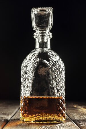 bottle of whiskey, or rum, or alcohol stands creative photo.