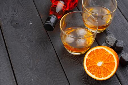 Whiskey and whiskey stones on a wooden table creative photo. Reklamní fotografie