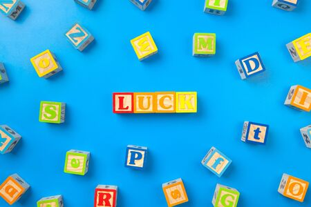Luck. Wooden colorful alphabet blocks on blue background, flat lay, top view. creative photo.