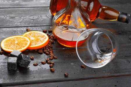 Whiskey or liqueur, coffee beans and orange cut on wooden background. Seasonal holidays concept. creative photo.