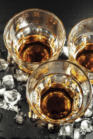 Whiskey and ice on rustic wood background