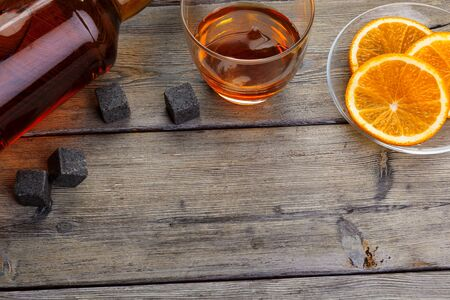 Whisky glass with orange fruit cut on dark wooden background. creative photo.