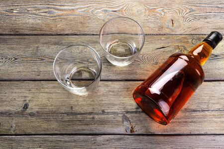 Whisky bottle on dark wooden background flat lay