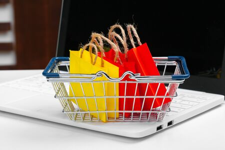 Online shopping concept. Shopping cart, laptop on the desk. 版權商用圖片