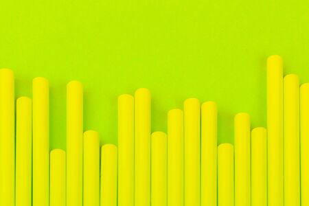 Drinking straws on bright neon green background. Close up. Imagens