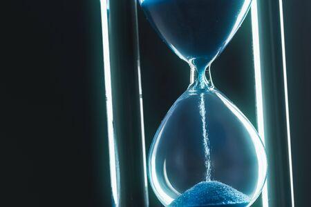 Hourglass on dark background. Close up.