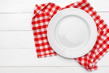 Empty plate and towel over wooden table background. Close up.