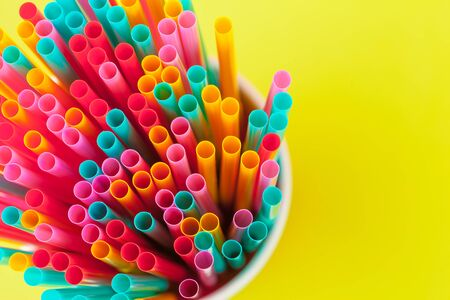 Colorful straws for beverage soft drink on colored background. Close up.