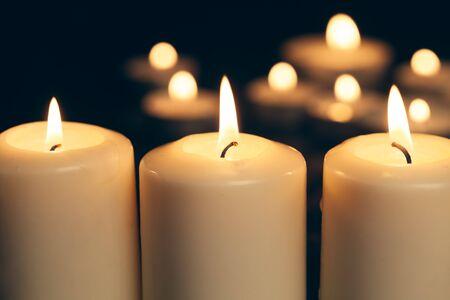 Kerzen brennen in der Dunkelheit auf schwarzem Hintergrund. Gedenkkonzept. Standard-Bild