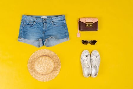 Set of female clothes and accessories on bright yellow background. Close up.