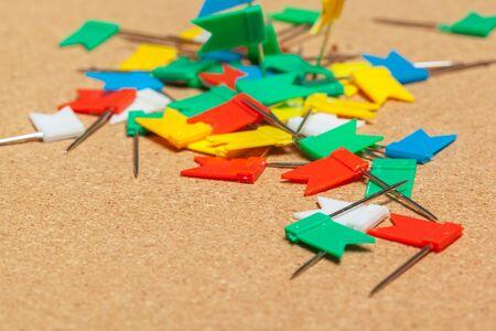 Mini flags thumbtacks over corkboard background close up