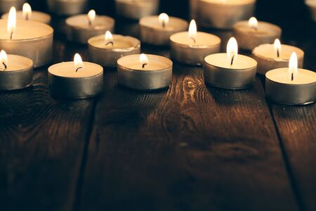 candles burning in darkness over black background. commemoration concept.