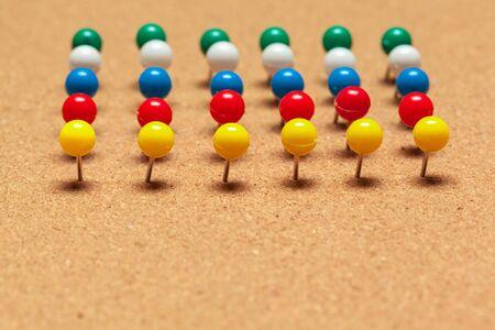 Group of thumbtacks pinned on corkboard in rows