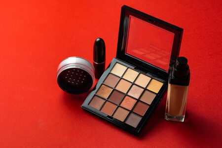 Set of cosmetics isolated over red background. Close up.