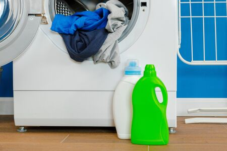 Bottle of detergent whith washing machine, indoors. Close up. Standard-Bild