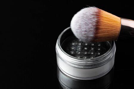 Make up powder with brush on black background, close up.