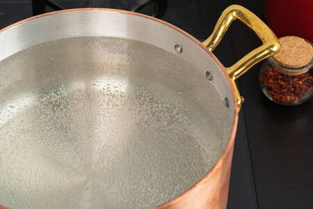 Copper pot with boiling water on a gas stove close up