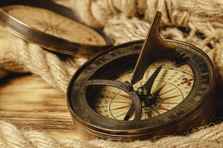 Ship rope and compass on wooden background, close up