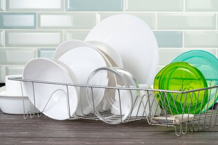 Dish rack with clean dry dishes on kitchen counter. Close up.