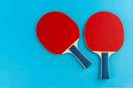 Red table tennis rackets on a blue background. Close up. Banque d'images