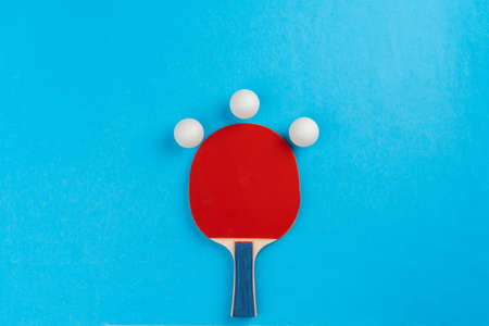 Table tennis racket and ball on blue background. Close up.
