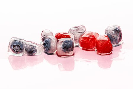 Fresh berries frozen in ice cubes for drinks. Close up. Фото со стока