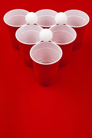 Cups and plastic ball on red background. Beer pong game. Close up.