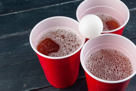 Wooden table with red cups and ball for beer pong. Close up.