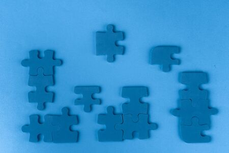 Puzzle pieces on classic blue background, top view