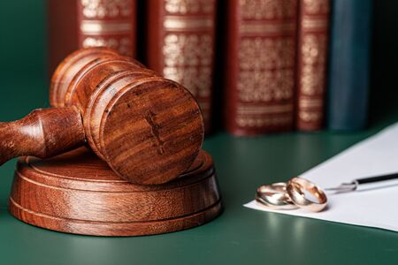Law gavel and wedding rings on table. Close up.
