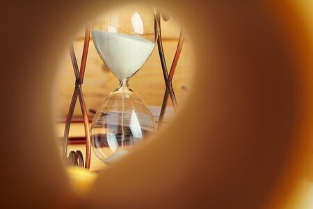 Close up of book page on a background of hourglass