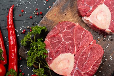 Two raw fresh marbled meat steak on dark background, cherry tomatoes and spices.