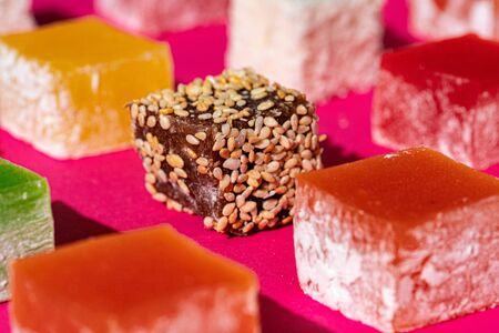 Turkish delight square pieces on a bright pink background close up