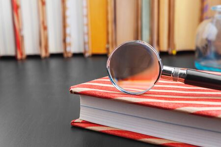 book and magnifying glass on wooden background. Close up.