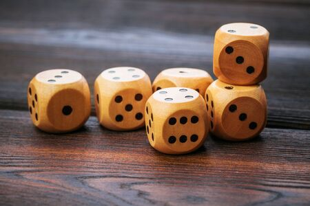 Dice on wooden table. Background for casino games. Close up.
