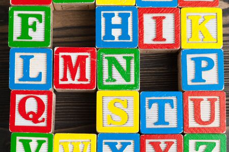 Alphabet blocks ABC on wooden table.