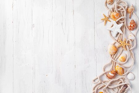 Sea shells with rope on white wooden background, copy space. Summer vacation concept Foto de archivo