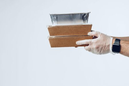 Courier hands in latex gloves giving packed food delivery