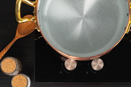 Copper pot with boiling water on a gas stove