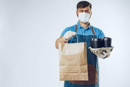 Delivery man in protective mask and medical gloves holding takeaway food. Compliance with the hygiene rules while covid-19 pandemic