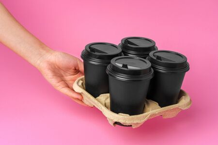 Coffee delivery. Human hand holding takeaway coffee cup