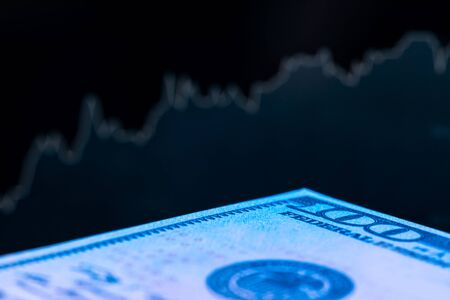 Dollars in front of a monitor with a price chart. Forex and trading. Close up.
