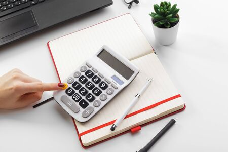 Business woman working with financial data hand using calculator. Close up.