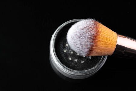 Make up powder with brush on black background Foto de archivo