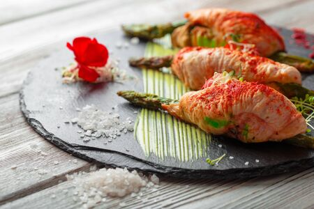 Asparagus rolled with chicken meat slices served on dark plate. Close up.