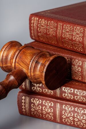 Brown wooden gavel with stack of books on gray table. Close up.
