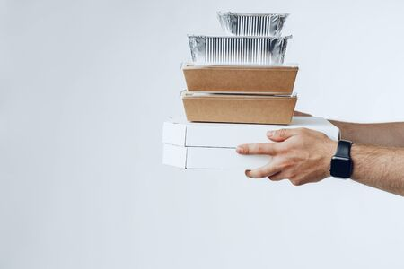 Courier hands giving packed food delivery close up against grey background