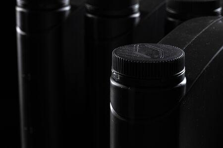 Engine oil bottle on black background, close up.